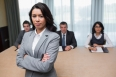 Serious businesswoman standing in front of business panel