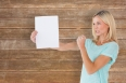 Angry woman holding piece of paper against wooden planks background