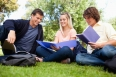 Low angle-shot of three students in a park studying