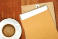 Brown Envelope document and a white coffee cup on a wooden desk