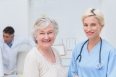 Portrait of nurse and senior patient smiling in clinic